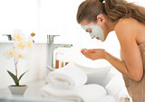Young woman wearing facial cosmetic mask washing face