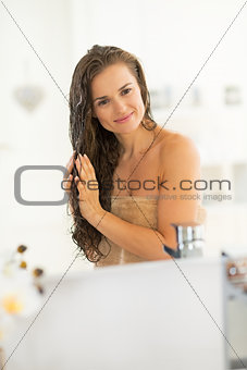 Portrait of happy young woman with wet hairs in bathroom