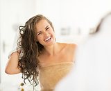 Portrait of smiling young woman wiping hair with towel