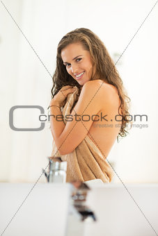 Portrait of happy young woman with long wet hair in bathroom