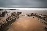 Long exposure landscape beach scene with moody sky