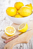 fresh lemons in a bowl and knife
