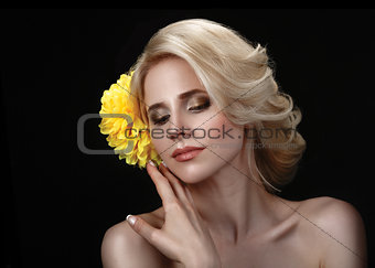 Beautiful young blond woman on a black background with a yellow