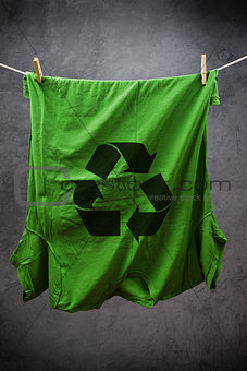 Green t shirt with recycle symbol hanging on rope to dry