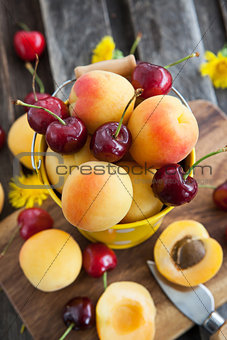 Fresh apricot and cherry in a bucket