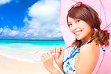 young woman holding a umbrella with beach background