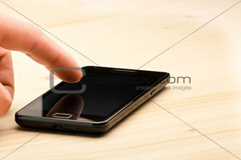 man's hand touching screen of black smartphone on wood desk