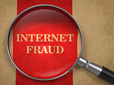Internet Fraud. Magnifying Glass on Old Paper.
