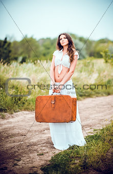 Beautiful young woman with suitcase in hands stands on rural road