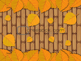 Autumn leaves over wooden planks
