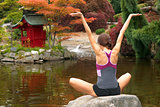 Woman Reaches for the Sky on Rock in Yoga Pond