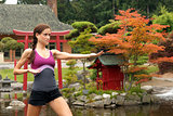 Fit Woman in Fighting Pose Near Yoga Pond Outside