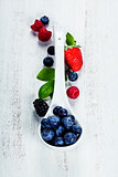 Berries with spoon  on Wooden Background.