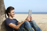 Happy man reading a tablet reader sitting on the beach