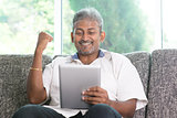 Indian man cheering while using tablet pc