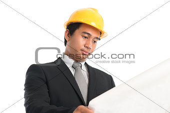 Asian male wearing yellow hardhat looking blue print paper.