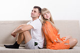 Couple sitting on couch with his back to each other