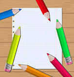 Colorful pencils on paper sheet background
