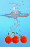 red tomatoes thrown into clear water