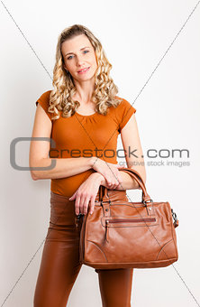 portrait of standing woman wearing fashionable brown clothes and