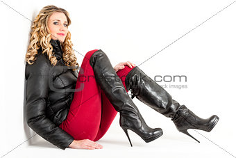 sitting woman wearing fashionable clothes with black boots