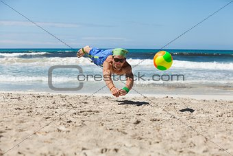 attractive adult man playing beach volleyball in summer