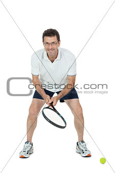 smiling adult tennis player with racket isolated