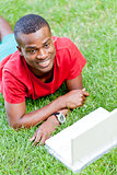 young smiling african student sitting in grass with notebook