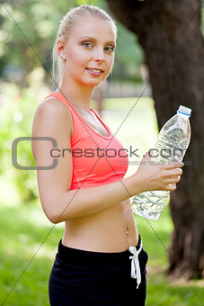 attractive young blonde woman drinking water outdoor sport