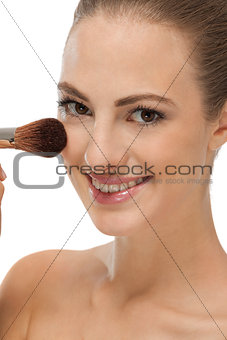 apllying powder make up on face portrait