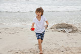 cute little boy playing in sand on beach in summer