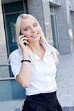 smiling attractive blonde businesswoman with smartphone