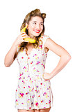 Retro pin up girl chatting on banana telephone