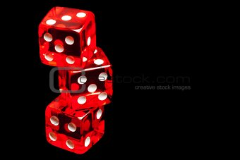 three red dice on black background