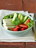 salad in asian style with tofu cheese, avocado and tomato