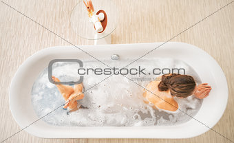 Young woman laying in bathtub