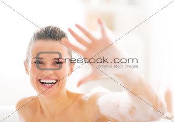 Portrait of happy young woman in bathtub showing foam