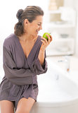 Happy young woman with apple near bathtub