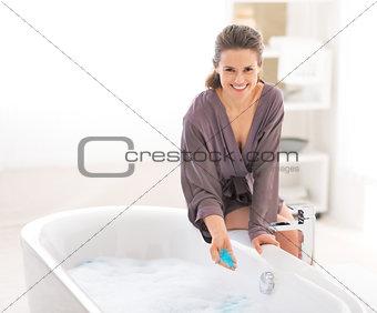Happy young woman adding bath salt in bathtub