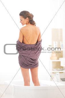 Young woman standing in bathtub. rear view