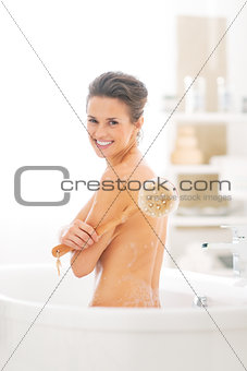 Portrait of happy young woman with body brush in bathtub