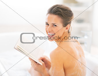 Portrait of happy young woman reading book in bathtub