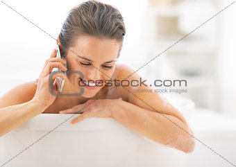 Happy young woman talking cell phone in bathtub