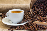 fresh espresso coffee in white cup  with roasted coffee beans