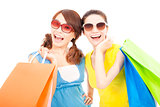happy young sisters holding shopping bags
