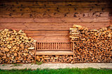 Empty wooden bench with pile of firewood