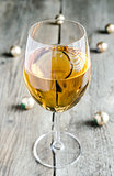 Wineglass with white wine and chocolate candies behind
