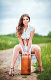 Beautiful young woman sits on a suitcase near rural road