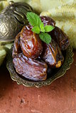 sweet dried dates in bowl on a wooden table