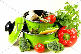 green pots full of vegetables (tomatoes, asparagus, mushrooms, broccoli) and pasta